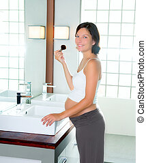 Beautiful pregnant woman on modern bathroom makeup with...