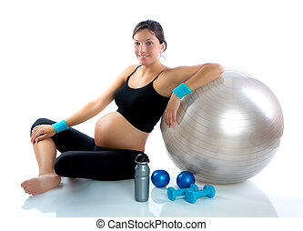 Beautiful pregnant woman at fitness gym relaxed with...
