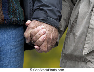 mature couple holding hands - casual couple in their 60s...