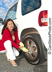 Woman changing car tyre - Closeup of unhappy senior woman...