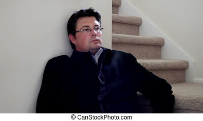 Depressed man sitting on stairs in winter coat