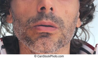 close up of a man smoking - unshaven man smoking cigarette