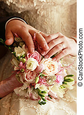 Wedding rings - Hands of the groom and the bride on a...
