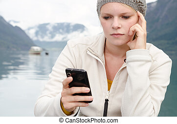 have young blond woman with her Smartphone in the hand and a...