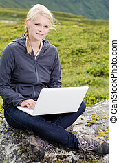 young blond woman sits with a laptop on a stone