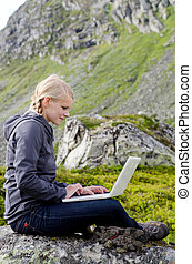young blond woman sits with a laptop on a stone before...