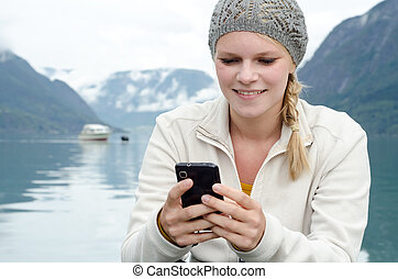 young blond woman with her Smartphone in the hand and a...