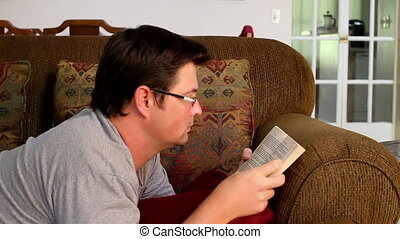 Man reading a book on couch