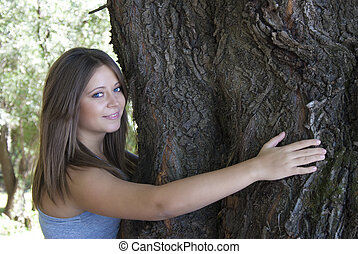 Love nature - Beautiful young girl hugging a tree