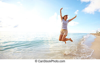 Happy woman jumping on the beach. Resort.