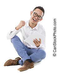 Asian man sitting on floor using tablet - Fullbody happy...