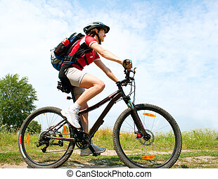 Happy Young Woman riding bicycle outside. Healthy Lifestyle