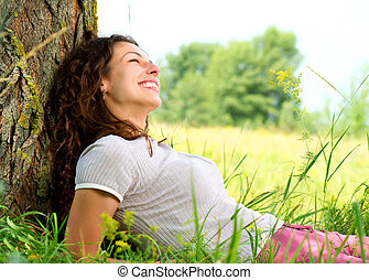 Beautiful Young Woman Relaxing outdoors Nature