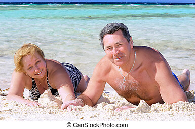 Mature couple on the beach in the tropics. - Mature couple...