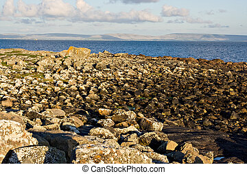 Galway Bay with a large rock jetty in the foreground. The...