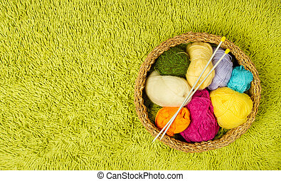 Knitting yarn balls and needles in basket over green carpet...