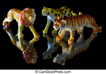 Toy animals: Lion, Cheetah and a Tiger on a black background...