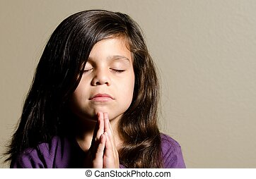 Praying - a little girl shows that she is praying
