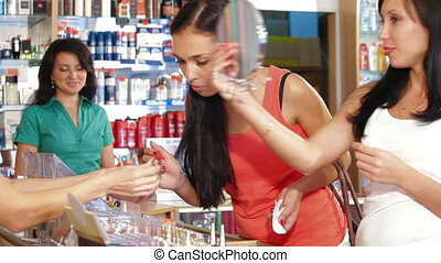 Female Friends Testing Lipstick in Beauty Department