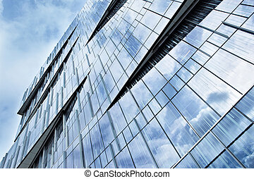 Corporate building full of glass windows reflecting the sky...