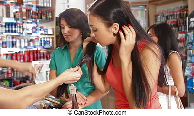 Women Choosing Hair Dye - Sales Person Assisting Female...
