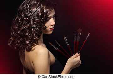 Beautiful girl with makeup brushes on black background