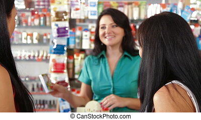 Shopping in Cosmetics Store - Young women shopping in...