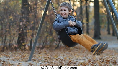 Autumn swing chair - Happy boy swinging on a swing in autumn