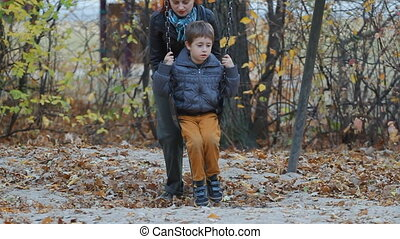 Autumn swing chair - Mom Pushing her son on a swing in a...
