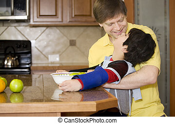 Father helping disabled son with work in the kitchen -...