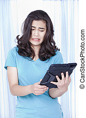 Teen girl looking with disgust at computer tablet in hand -...