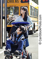 Big sister pushing disabled brother in wheelchair at school...