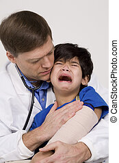 Male doctor in early forties comforting scared five year old disabled patient during office visit
