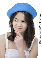 Beautiful young teen girl in blue hat, looking over with...