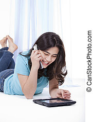 Teen girl playing with tablet computer and using phone -...