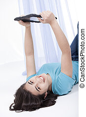 Teen girl playing with tablet computer on the floor -...