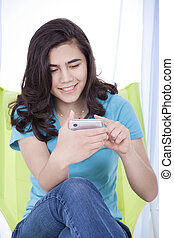 Teen girl texting on a cell phone - Biracial teen girl or...