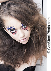 Young woman with creative face-art - carnival fantasy