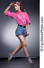 Young running woman in elegant jeans shorts, studio shot -...