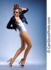Young sexy fashion dancing woman isolated in sunglasses -...