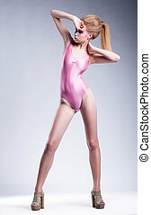 Sexy young woman blonde in swimsuit posing in studio -...