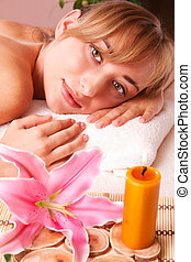 Beatiful women relax in spa, lily and candle