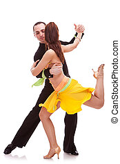 nice salsa dancing couple with the woman holding one leg in...