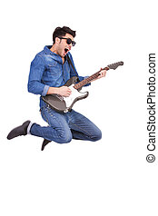 young man jumping with guitar - casual young man jumping and...