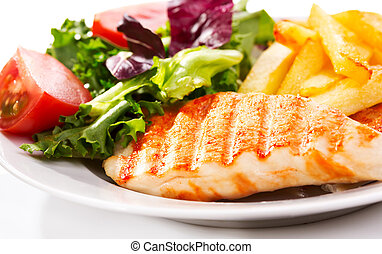 Grilled chicken breast with fries and salad