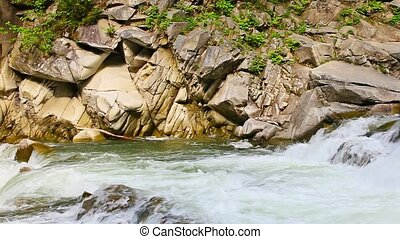 Mountain river flowing around rocks