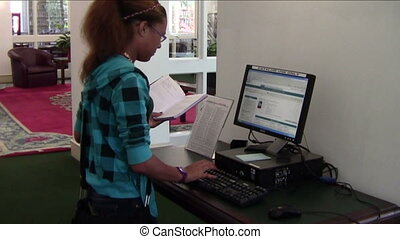 Library research - High school student searching library...