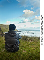 Solitude - A young man sittin on the grass enjoying the...