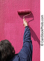 Painting of red wall with paint roller