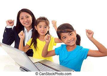 Smiling girls using a laptop